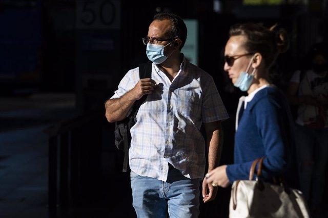 Un hombre y una mujer caminan en el centro de una ciudad.