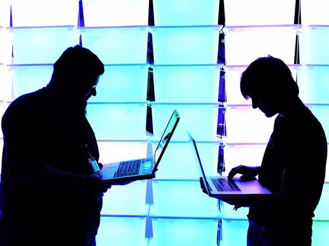 Archivo - Dos personas sostienen sus portátiles durante un congreso de hackers en Alemania.