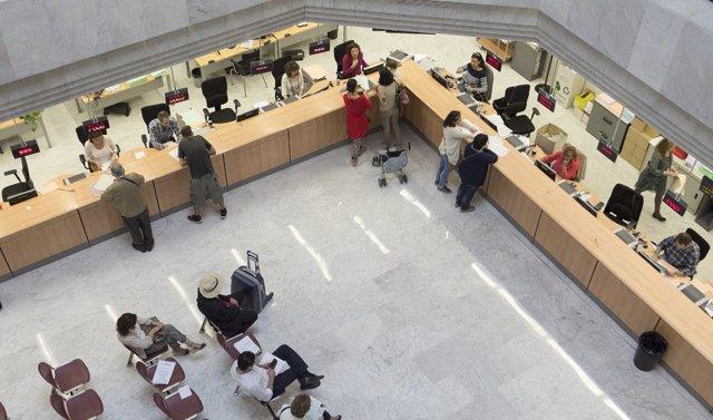 Archivo - Funcionarios atendiendo al público en una sede de la administración de la Junta de Andalucía.