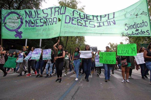 Archivo - Mujeres sostienen pancartas y carteles durante una protesta a favor de la legalización del aborto.