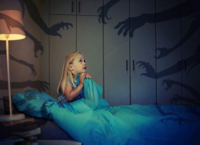 Archivo - Niña con miedo en la cama.