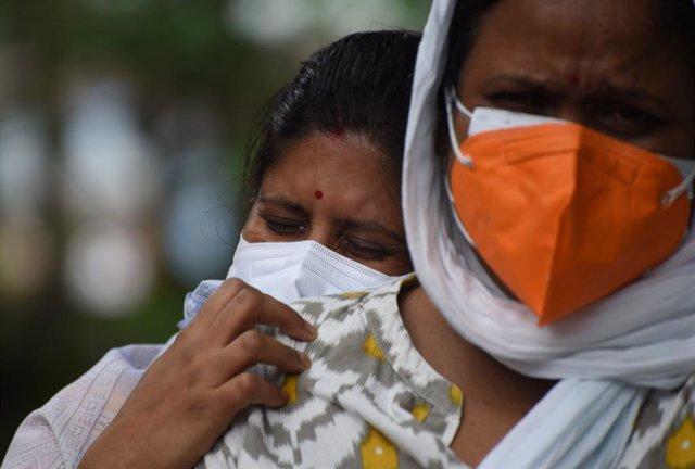 Familiares de una persona fallecida por coronavirus en India