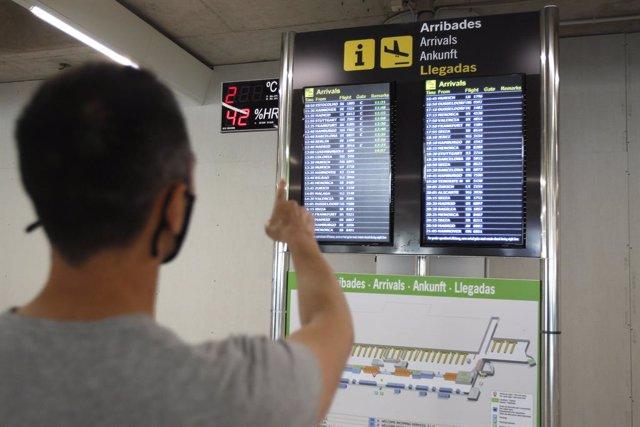 Archivo - Un pasajero señala la pantalla del aeropuerto de Palma.