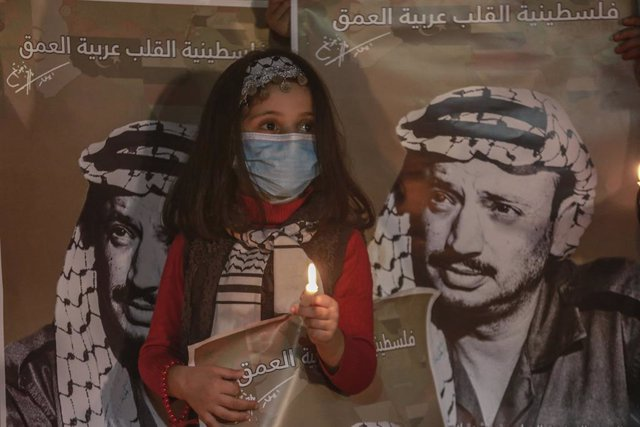 Archivo - 10 November 2020, Palestinian Territories, Gaza City: A Palestinian girl holds a candle inside the home of late Palestinian political leader Yasser Arafat in Gaza City during a ceremony to commemorate the 16th anniversary of the death of the lat