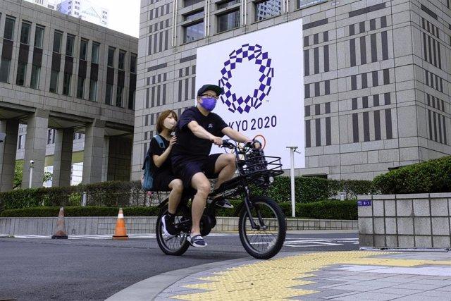 Una pareja pasea en bici por delante del cartel de los Juegos Olímpicos de Tokyo 2020.