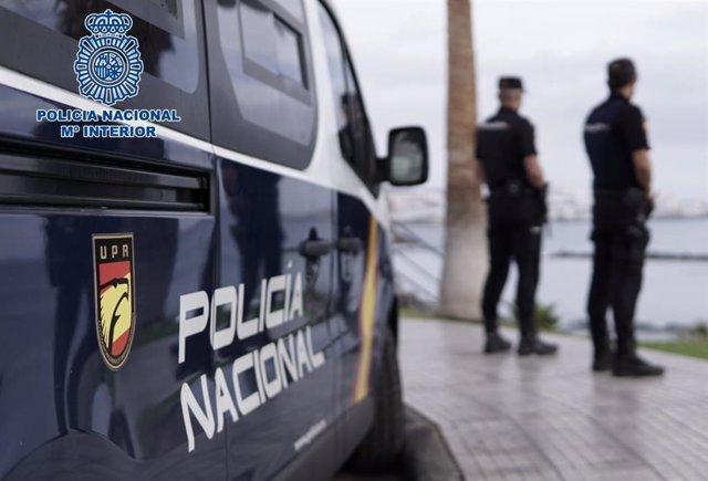 Archivo - Agentes de la Policía Nacional junto a un coche patrulla