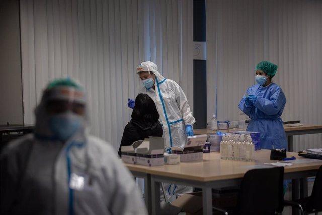 Archivo - Una mujer recibe una prueba PCR.