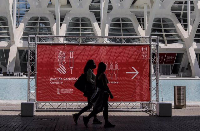 Archivo - Dos personas pasan por un cartel que indica el punto de vacunación de la Ciudad de las Artes y las Ciencias de Valencia