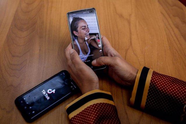 Archivo - Una persona mira en su móvil el vídeo de una joven en la red musical Tik Tok, en Madrid (España), a 22 de septiembre de 2020. TikTok ha publicado este martes su tercer Informe de Transparencia, que recoge la actividad del primer semestre de 2020