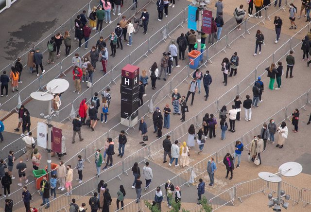 19 June 2021, United Kingdom, London: People queue outside an NHS Vaccination Clinic at West Ham's London Stadium in Stratford, east London. The NHS is braced for high demand as anyone in England over the age of 18 can now book a Covid-19 vaccination jab.