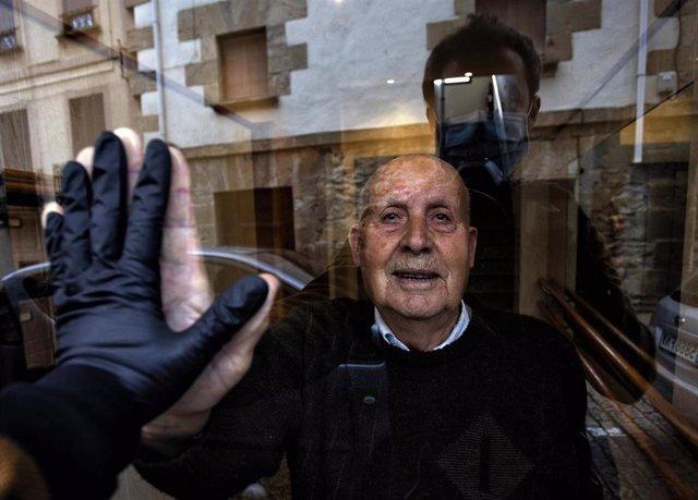 Archivo - Visita a mi abuelo Miguel, de 90 años, durante el confinamiento que saluda a través del cristal del portal.  Huarte, Navarra, 1 de abril, 2020. ( ( Unai Beroiz)