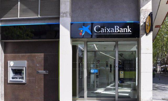 Cambio de la rotulación en una oficina de Bankia, ahora de CaixaBank.