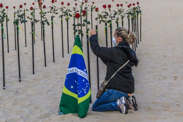 20 June 2021, Brazil, Rio de Janeiro: A woman puts a rose during a protest by activists of the NGO Rio de Paz on Copacabana beach, where they placed 500 roses in the sand to commemorate the deaths of 500,000 Brazilians of Coronavirus (Covid-19) in the cou