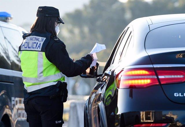 Archivo - Un agente de policía le pide la documentación a un conductor en un control en un punto fronterizo entre Portugal y España, a 5 de abril de abril de 2021, en Zarza la Mayor, Cáceres, (España). En el dispositivo, puesto en marcha entre los puntos