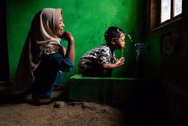 Archivo - Wahyu observa a su hijo Rizki, de 4 años, lavándose la cara en una nueva instalación de agua potable en su casa, en Tlogopakis, Indonesia.