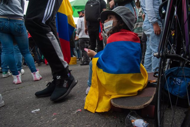 Archivo - Una niña se sienta en una patineta con una bandera de Colombia envuelta en su espalda en una jornada de protestas en Bogotá.