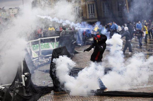 Archivo - Manifestantes en medio del humo de los botes de gas lacrimógeno durante los disturbios tras una protesta contra el Gobierno del presidente Iván Duque y la violencia policial.