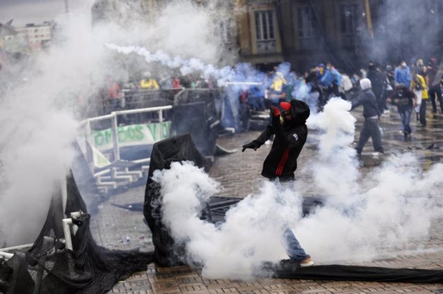 Archivo - 05 May 2021, Colombia, Bogota: Demonstrators stand amid smoke from tear gas canisters during rioting following a protest against President Duque's government and police violence. Photo: Sergio Acero/colprensa/dpa