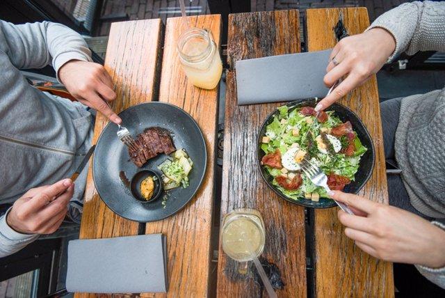 Archivo - Gente comiendo en un restaurante