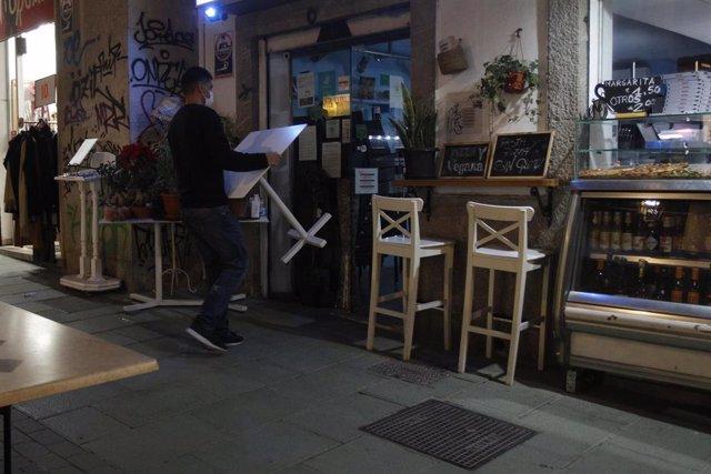 Archivo - Un camarero recoge las mesas de la terraza de una cafetería en Palma.