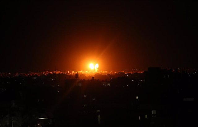 17 June 2021, Palestinian Territories, Gaza City: Explosions light-up the night sky above buildings in Gaza City as Israeli forces shell the Palestinian enclave. The Israeli military tweeted on Thursday night that the bombardments of military compounds an