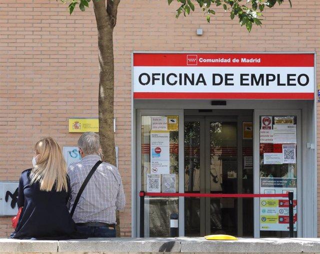 Dos personas sentadas frente a una oficina del SEPE, el día en el que se han conocido los datos de paro de mayo, a 2 de junio de 2021, en Madrid (España).