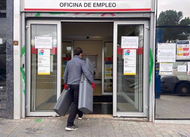 Archivo - Un hombre entra a una oficina de empleo