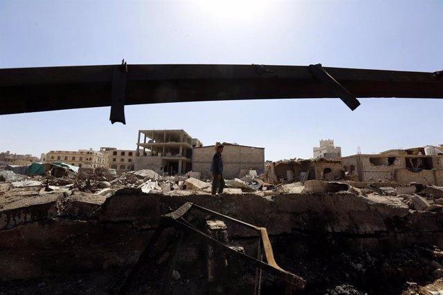 Archivo - Un hombre camina entre los restos de una explosión en Yemen.