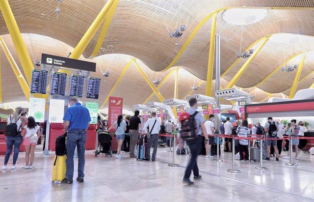 Varias personas hacen cola con equipaje en la T4 del aeropuerto Adolfo Suárez, Madrid-Barajas, a 1 de julio de 2021, en Madrid (España)
