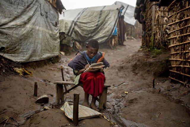 Archivo - Una niña hace sus deberes en un campo de desplazados internos en Masisi, en RDC