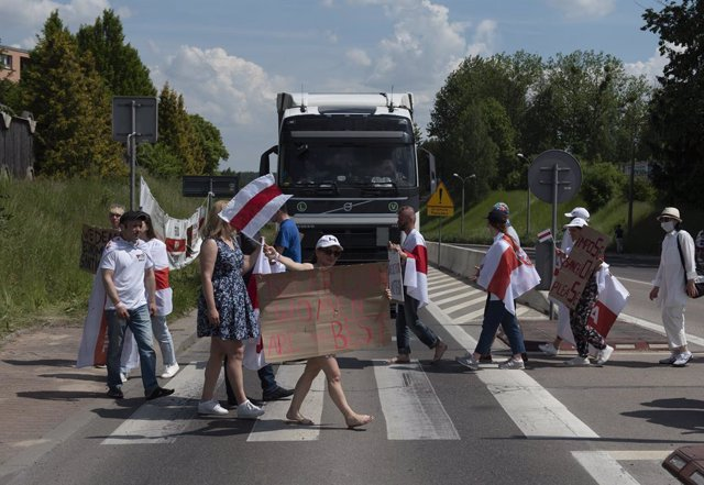 08 June 2021, Poland, Warsaw: Demonstrators wave historical Belarus opposition flags and hold placards duringa  protest at the Polish-Belarusian against the Belarusian President Alexander Lukashenko. Photo: Aleksander Kalka/ZUMA Wire/dpa