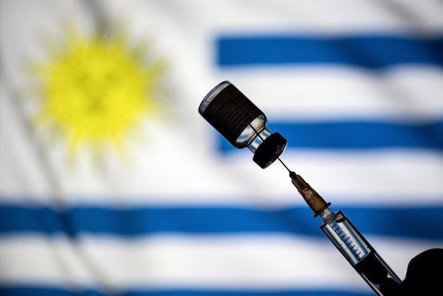 Archivo - Montaje de una vacuna con la bandera de Uruguay