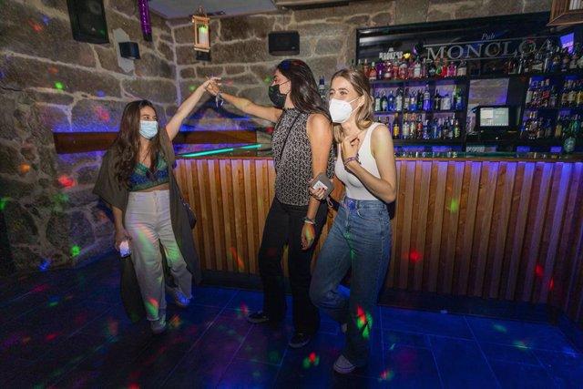 Un grupo de jóvenes disfrutan de la primera noche de la reapertura del ocio nocturno con condiciones en Galicia, a 1 de julio de 2021, en Pontevedra, Galicia (España). A partir de hoy, la Xunta de Galicia permite la reapertura de los locales de ocio noctu