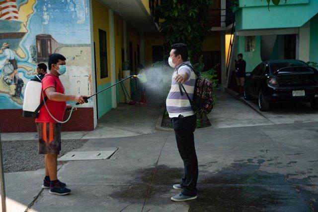 Archivo - Un migrante hondureño es desinfectado tras su llegada Guatemala en plena pandemia.
