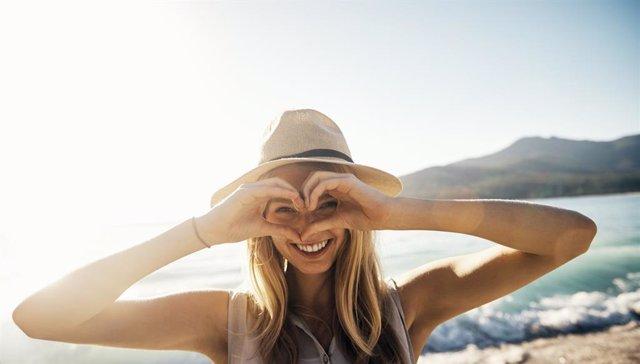 Archivo - Mujer sonriendo haciendo un corazón con las manos en la playa.