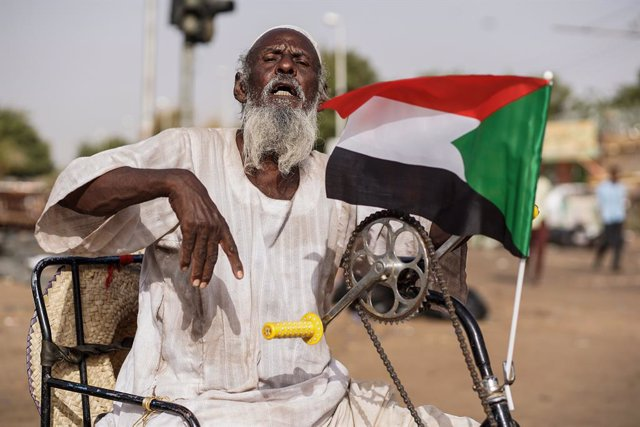 Archivo - 12 April 2019, Sudan, Khartoum: A Sudanese man holds the national flag as he sits on a wheel chair during a sit-in protest outside the Defence Ministry, to demand the formation of a civilian government, a day after the military took power and ar