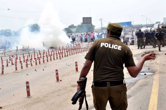 Archivo - 11 August 2020, Pakistan, Lahore: A police officer attempts to throw a stone towards Pakistan Muslim League (PML-N) members as clash with each other outside the National Accountability Bureau (NAB) office where party leader Maryam Nawaz had arri
