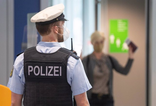 29 June 2021, Hessen, Frankfurt: A police officer stands to check passengers on a flight from Portugal at Frankfurt airport. As of today, the country is considered a virus variant area. After arriving in Germany, passengers must go into quarantine. Photo: