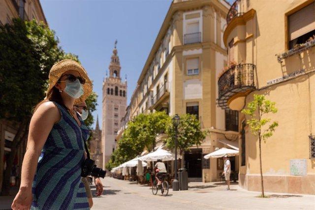 Turistas pasean por el centro de Sevilla provistos de gorras, abanicos y botellas de agua