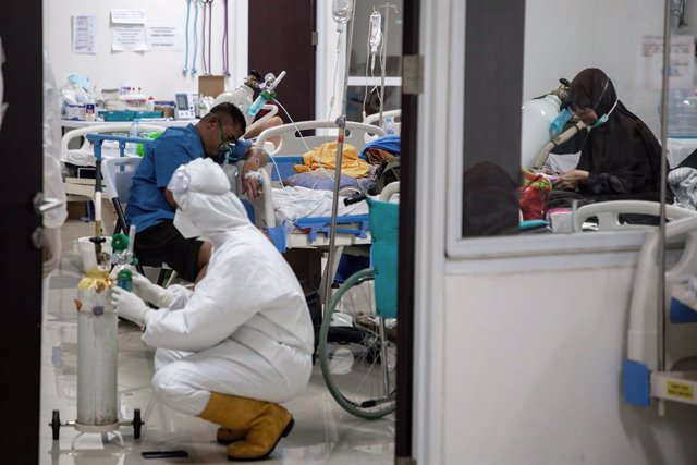 28 June 2021, Indonesia, Jakarta: A health worker wearing a Personal Protective suit fixes an oxygen cylinder next to a COVID-19 patient inside the Wisma Atlet Covid-19 Emergency Hospital complex. Photo: Risa Krisadhi/SOPA Images via ZUMA Wire/dpa