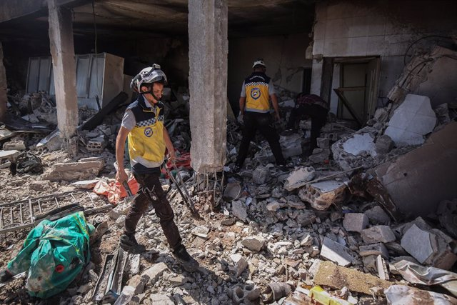 03 July 2021, Syria, Sahl ar Ruj: Members of the Syria Civil Defence, known as White Helmets, inspect the rubble of a damaged Civil Defence centre after it was targeted by warplanes. According to a war monitor, Russian aircraft allegedly carried out the a