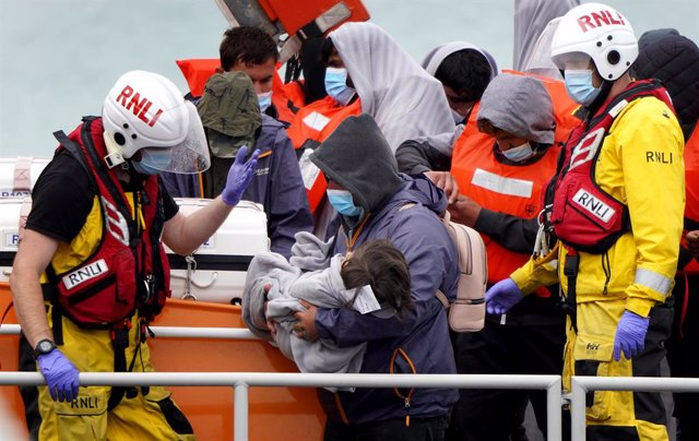 02 July 2021, United Kingdom, Dover: A man carries a young child as a group of people thought to be migrants are brought in to Dover following a small boat incident in the English Channel earlier this morning. Photo: Gareth Fuller/PA Wire/dpa