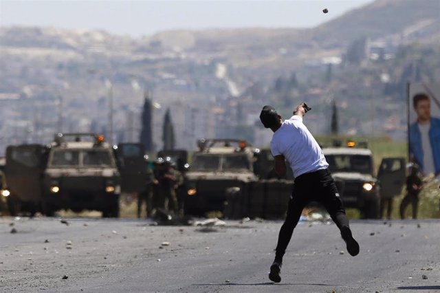 Archivo - Un manifestante palestino frente a fuerzas militares israelíes en Cisjordania