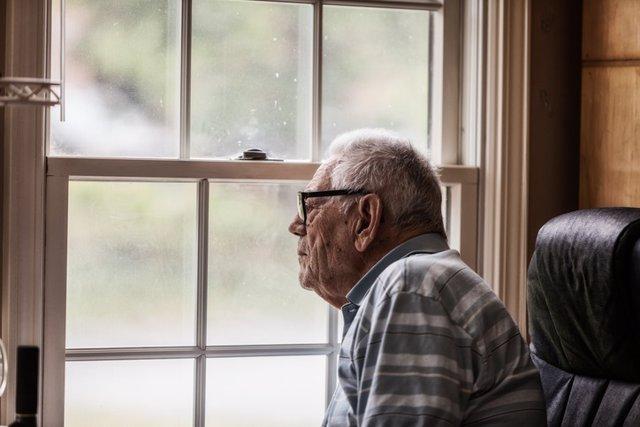 Archivo - Senior Man Staring Through Grungy Window