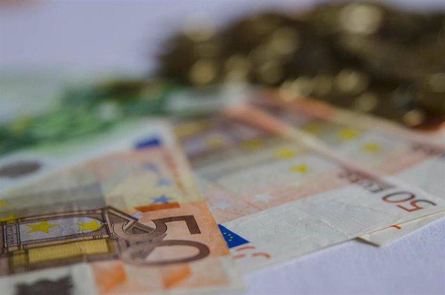 Archivo - Billetes y monedas en euros