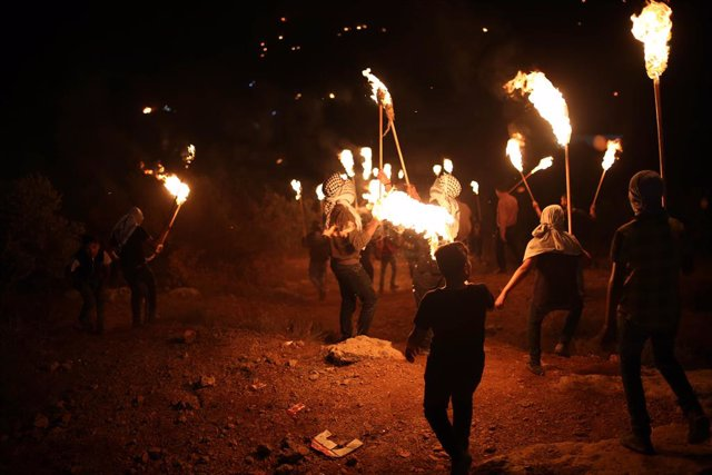 23 June 2021, Palestinian Territories, Nablus: Palestinians carry torches during a night demonstration against the expansion of a Jewish settlement on the lands of Beita village. Photo: Shadi Jarar'ah/APA Images via ZUMA Wire/dpa