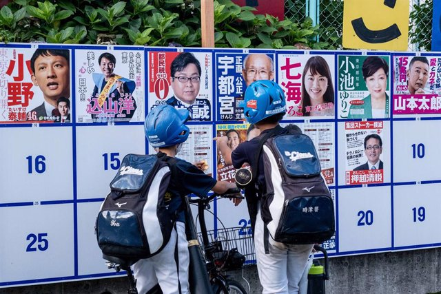 Archivo - 05 July 2020, Japan, Tokyo: Teenagers look at an election board with candidates posters during Tokyo Gubernatorial Election 2020. Photo: Viola Kam/SOPA Images via ZUMA Wire/dpa