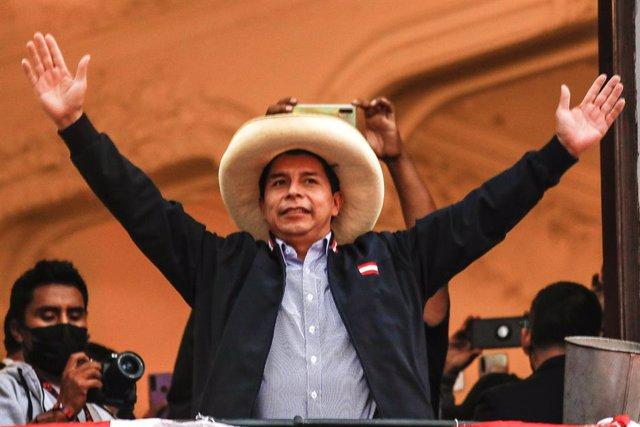 El candidato presidencial Pedro Castillo de Perú Libre saluda a sus partidarios en el balcón de la sede de su partido político después de una reñida segunda vuelta contra la candidata presidencial de Fuerza Popular Keiko Fujimori.