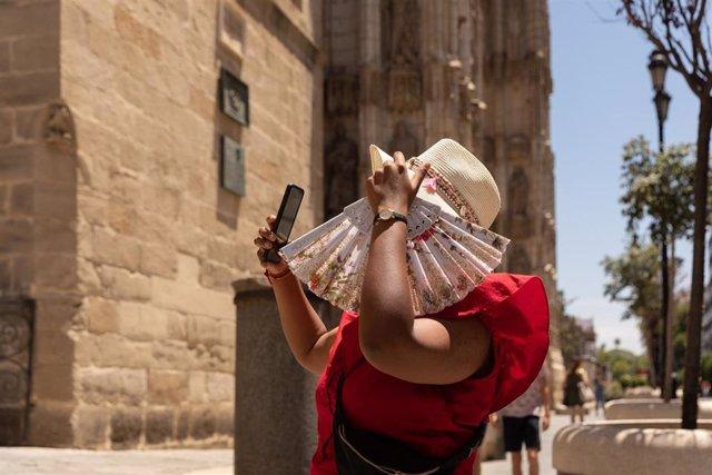 Turistas pasean por el centro de Sevilla provistos de gorras, abanicos y botellas de agua debido a que la capital andaluza ha superado los 40ªC y por ello se ha activado la alerta amarilla a 08 de junio del 2021, en Sevilla, Andalucía, España