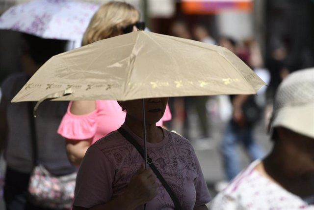 Archivo - Mujer bajo un paraguas en un día caluroso.